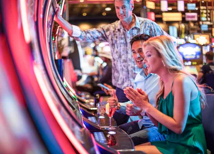 Woman playing slots while friends look on