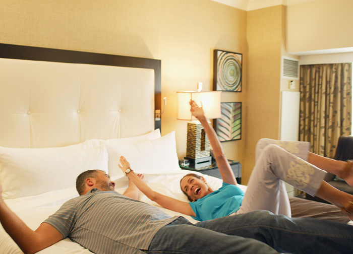 Young couple falling back on their bed