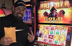 Jackpot winner Joseph S. standing by a slot machine