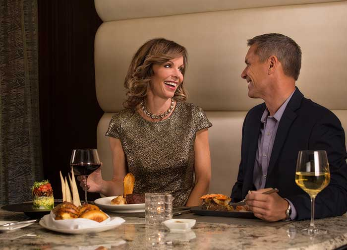 Middle-aged couple enjoying fine dining at Atlantis Steakhouse