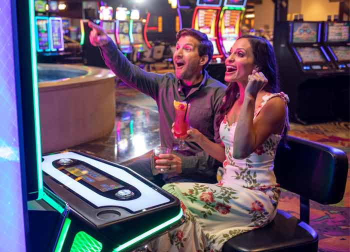Couple playing slots on casino floor at Atlantis