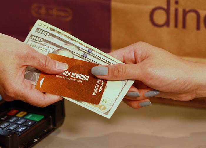 Woman handing cash and Monarch Rewards card to cashier
