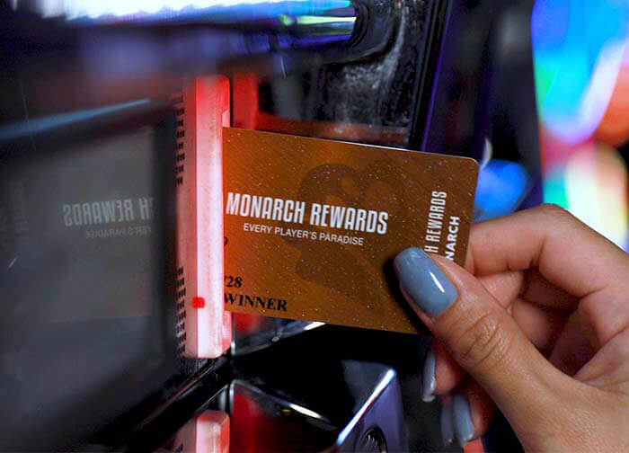 Woman inserting Monarch Rewards card into slot machine