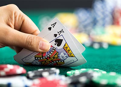 Hand with 21 lifting blackjack cards off table