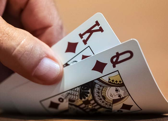 Hand lifting blackjack cards to reveal 21