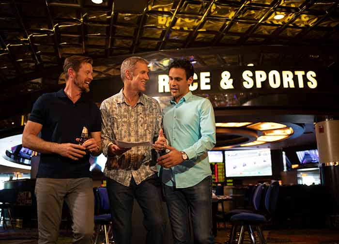 3 friends discussing sports wagers at the Sports bar and Lounge